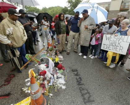 Rev. Jessie Jackson pauses at a makeshift memorial for Michael Brown Saturday, Aug. 16, 2014, located at the site where Brown was shot by police a week ago in Ferguson, Mo.