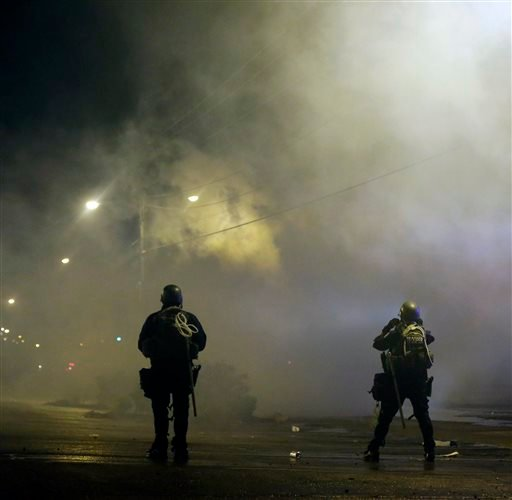 A law enforcement watch Sunday, Aug. 17, 2014, after tear gas was fired to disperse a crowd protesting the shooting of teenager Michael Brown last Saturday in Ferguson, Mo.