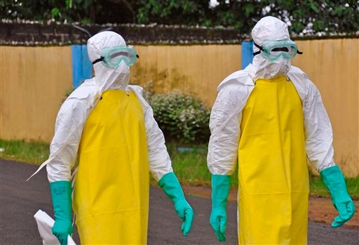 Health workers wearing protective gear go to remove the body of a person who is believed to have died after contracting the Ebola virus in the city of Monrovia, Liberia, Saturday, Aug. 16, 2014.