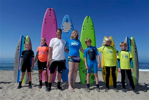 In this July 24, 2014 photo, the Montelone family, from left, Grace, 8, Brooke, 10, Rob, Paulette, Brian, 10, Michael, 12, and Gavin, 8, pose for a family picture on the beach in San Clemente, Calif.
