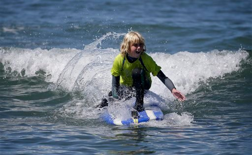 In this July 24, 2014 photo, Michael Montelone, 10, rides a wave in San Clemente, Calif.