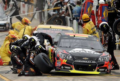 Jeff Gordon (24) and Joey Logano make pit stops during the NASCAR Sprint Cup Series Pure Michigan 400 auto race at Michigan International Speedway in Brooklyn, Mich., Sunday, Aug. 17, 2014. (AP Photo/Paul Sancya)