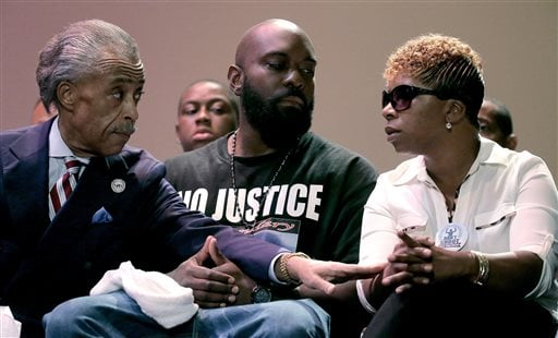 Rev. Al Sharpton speaks with parents of Michael Brown, Michael Brown Sr. and Lesley McSpadden during a rally at Greater Grace Church, Sunday, Aug. 17, 2014, for their son who was killed by police last Saturday in Ferguson, Mo.