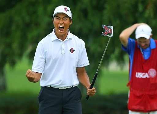 Gunn Yang, of San Diego, Calif., and his caddy Richard Grice react to sinking his par putt on the 17th hole during the afternoon round to win the 36-hole championship match of the 2014 U.S. Amateur Championship at Atlanta Athletic Club on Sunday, Aug.17..