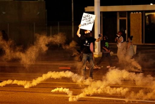 A protester stands in the street after police fired tear gas to disperse a crowd Sunday, Aug. 17, 2014, during a protest for Michael Brown, who was killed by a police officer last Saturday in Ferguson, Mo.