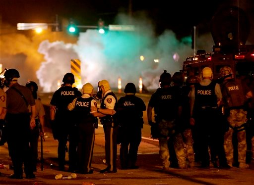 Police wait to advance after tear gas was used to disperse a crowd Sunday, Aug. 17, 2014, during a protest for Michael Brown, who was killed by a police officer last Saturday in Ferguson, Mo.