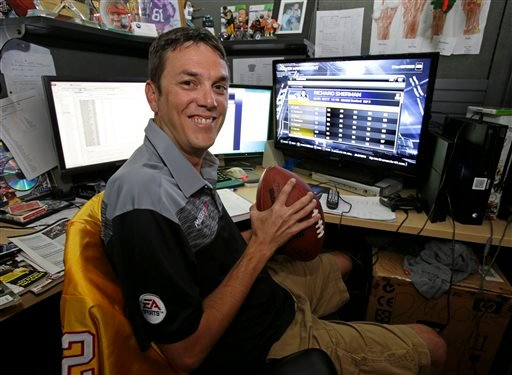 In this Wednesday, Aug. 6, 2014 photo, Donny Moore poses for a photo in front three computer screens he uses to rate NFL football players for the Madden NFL video football game at EA Sports in Orlando, Fla.