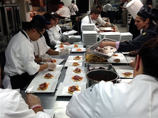 In this Sept. 26 2013 photo, staff members prepare dishes of slow-cooked beef served with gnocchi fashioned out of McDonald's french fries and a fruit sauce from its smoothie mix during a dinner hosted by McDonald's for reporters and bloggers, in New York