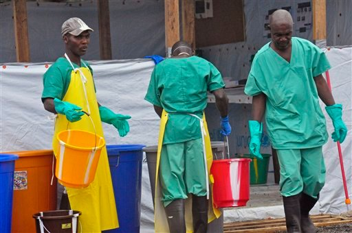 Health workers with buckets, as part of their Ebola virus prevention protective gear, at an Ebola treatment center in the city of Monrovia, Liberia, Monday, Aug. 18, 2014.