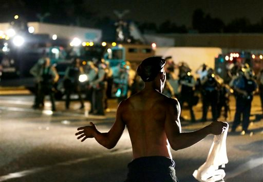 A man stands in front of police during a protest Monday, Aug. 18, 2014, for Michael Brown, who was killed by a police officer Aug. 9 in Ferguson, Mo. (AP)