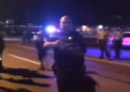 The image is taken from a YouTube video of an officer pointing his gun at protesters.