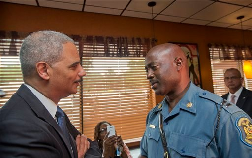 Attorney General Eric Holder speaks with Capt. Ron Johnson of the Missouri State Highway Patrol at Drake's Place Restaurant, Aug. 20, 2014, in Ferguson, Mo. (AP Photo/Pablo Martinez Monsivais, Pool)
