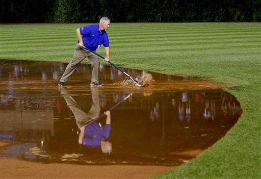 A member of the grounds crew works on the field after a heavy rain soaked Wrigley Field during the fifth inning of a baseball game between the San Francisco Giants and the Chicago Cubs on Tuesday, Aug. 19, 2014, in Chicago. (AP Photo/Jeff Haynes)