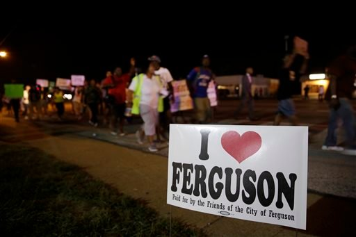 Protesters march Thursday, Aug. 21, 2014, in Ferguson, Mo. Protesters again gathered Thursday evening, walking in laps near the spot where Michael Brown was shot.