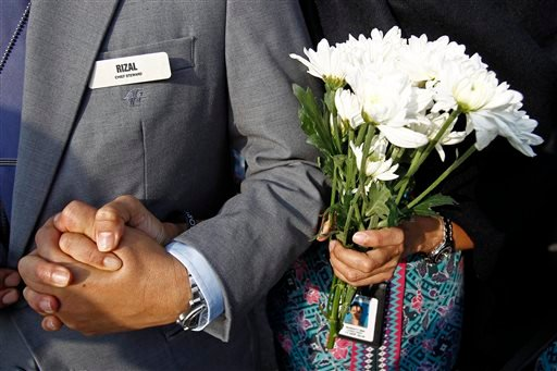 A Malaysia Airlines crew member holds flowers as she waits outside Bunga Raya Complex at Kuala Lumpur International Airport where victims' bodies of the ill-fated Malaysia Airlines Flight MH17 are scheduled to be flown back, in Sepang, Malaysia, Friday..