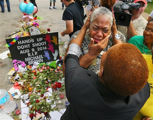 Spiritual teacher Iyanla Vanzant, right, consoles Shirley Scale, a resident at the Canfield Apartments, at the shrine to Michael Brown where he was shot and killed on Wednesday, Aug. 20, 2014, in Ferguson, Mo. (AP)
