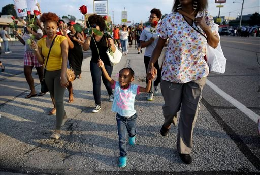 In this Aug. 18, 2014 file photo, a little girl holds a rose as she marches with protesters in Ferguson, Mo.