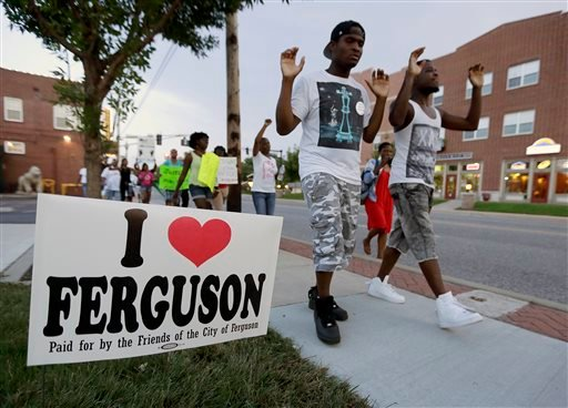 In this Aug. 20, 2014 file photo, people march to protest the shooting of Michael Brown in Ferguson, Mo.