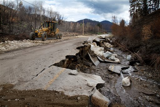 A road crew works to repair Highway 20 about eight miles south of Twisp, Wash. on Friday, Aug. 22, 2014, after mud and water flooded the area Thursday night.