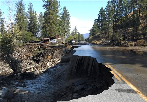 In this photo provided by Washington State Department of Transportation water pours over a damaged road east of Twisp, Wash., Friday, Aug. 22, 2014.