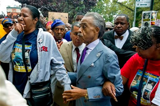 Esaw Garner, left, arrives at the spot where her husband Eric Garner died with The Rev. Al Sharpton, center, and Eric Garner's mother Gwen Carr, right, at the start of a march and rally in the Staten Island borough of New York, Saturday, Aug. 23, 2014.