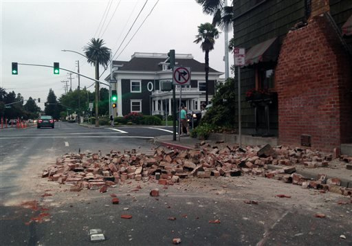 Bricks are in the street after a building was damaged during an earthquake in Napa, Calif., Sunday, Aug. 24, 2014.