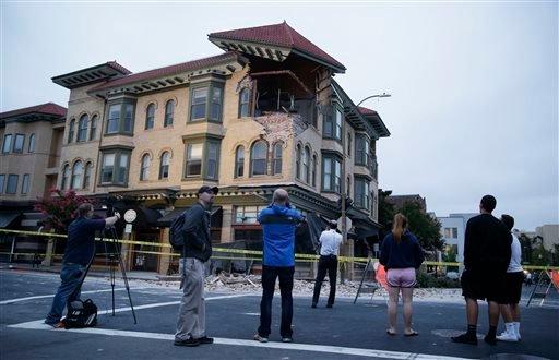 People look at a damaged building with a top corner exposed following an earthquake Sunday, Aug. 24, 2014, in Napa, Calif.
