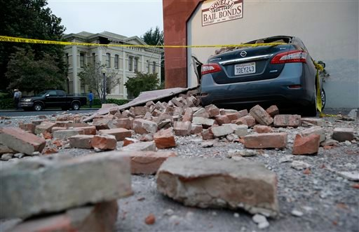 Bricks and fallen rubble cover a car with the old courthouse in the background following an earthquake Sunday, Aug. 24, 2014, in Napa, Calif.
