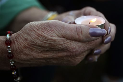 A woman holds a candle during a vigil for James Foley in his hometown of Rochester, N.H., Saturday, Aug. 23, 2014.
