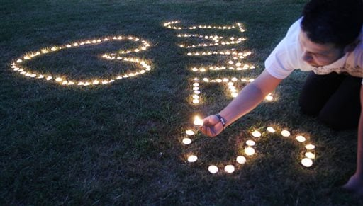 Candles are lighted on the town common during a vigil for James Foley in his hometown of Rochester, N.H., Saturday, Aug. 23, 2014.