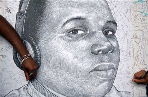 In a Monday, Aug. 18, 2014 file photo, protestors autograph a sketch of Michael Brown during a protest, in Atlanta.