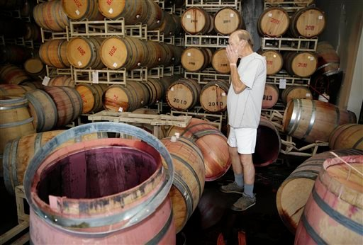 Winemaker Tom Montgomery stands in wine and reacts to seeing damage following an earthquake at the B.R. Cohn Winery barrel storage facility Sunday, Aug. 24, 2014, in Napa, Calif.