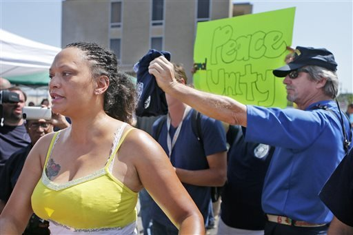 "Sondra Fifer, of St. Louis, voices her disagreement with the rally for Ferguson police Officer Darren Wilson on Saturday, Aug. 23, 2014, at Barney's Sports Pub in St. Louis. ""I'm not against officers, I'm against police brutality,"" Fifer said."