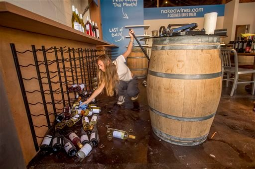 Grace Hardy cleans up wine bottles at nakedwines.com in Napa, Calif., following an earthquake Sunday, Aug. 24, 2014.