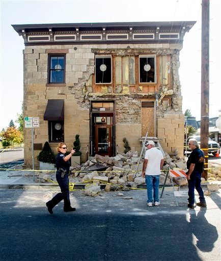A Napa police sergeant asks spectators to move further from the damaged Vintner's Collective tasting room in Napa, Calif., following an earthquake Sunday, Aug. 24, 2014.