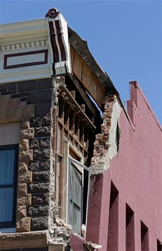 Part of a brick wall is missing from a building after an earthquake Sunday, Aug. 24, 2014, in Napa, Calif.