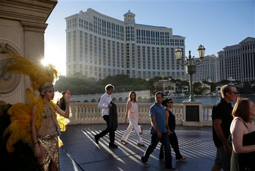 In this Friday, Aug. 15, 2014 photo, people walk by the Bellagio, in Las Vegas.