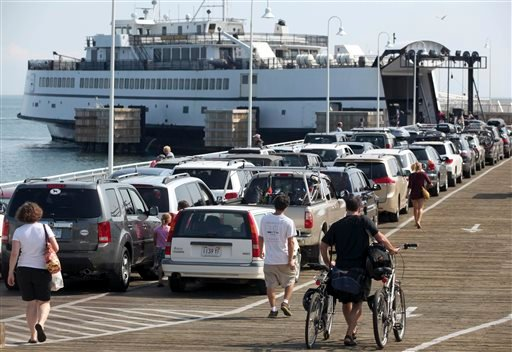 In this Aug. 26, 2011, file photo, passengers with cars and bicycles prepare to board a ferry departing the island of Martha's Vineyard, in Oak Bluffs, Mass.