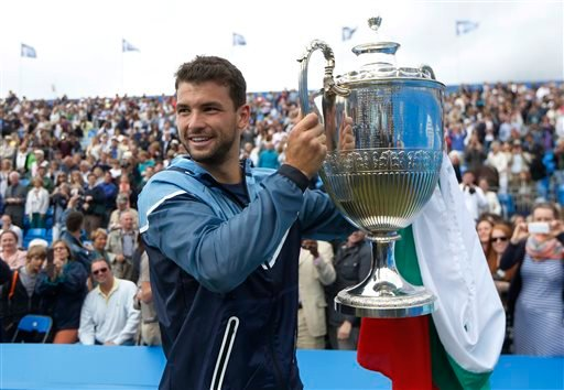 In this June 15, 2014, file photo, Grigor Dimitrov, of Bulgaria, poses with the trophy after his win against Feliciano Lopez, of Spain, at the end of their Queen's Club grass court championships singles final tennis match..