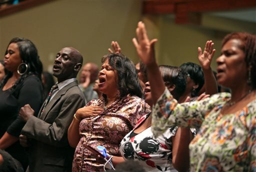 People attending the funeral services for Michael Brown sing on Monday, Aug. 25, 2014, at Friendly Temple Missionary Baptist Church in St. Louis.
