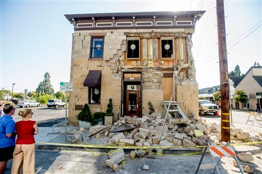 Pedestrians stop to examine a crumbling facade at the Vintner's Collective tasting room in Napa, Calif., following an earthquake Sunday, Aug. 24, 2014. (AP Photo/Noah Berger)