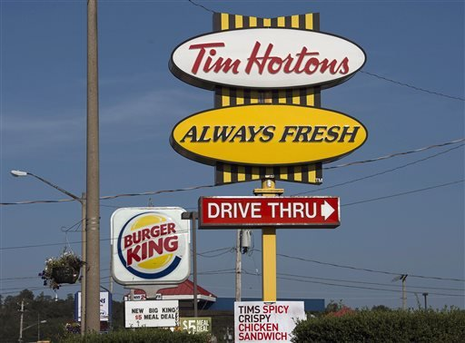 A Burger King sign and a Tim Hortons sign are displayed in Lower Sackville, Nova Scotia, Monday, Aug. 25, 2014. Burger King is in talks to buy Tim Hortons in hopes of creating a new, publicly traded company with its headquarters in Canada.