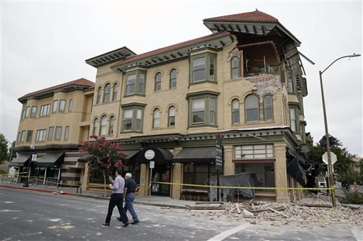 Two men walk past the earthquake-damaged building that housed the Carpe Diem wine bar Monday, Aug. 25, 2014, in Napa, Calif.