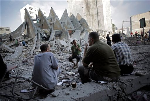 Palestinians have a coffee next to the rubble of the 15-story Basha Tower that collapsed from early morning Israeli airstrikes in Gaza City, Tuesday, Aug. 26, 2014.
