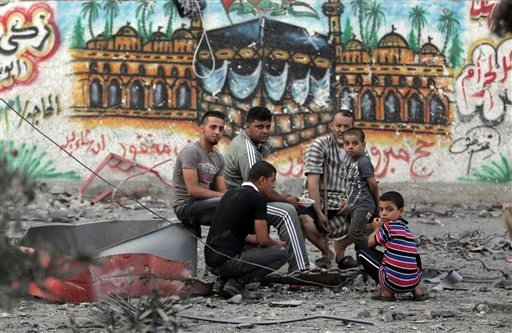 Palestinians rest amid the rubble of the 15-story Basha Tower that was leveled in early morning Israeli airstrikes, in Gaza City, Tuesday, Aug. 26, 2014.