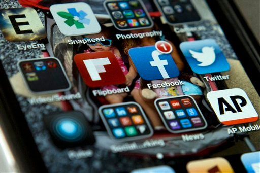 This May 21, 2013 file photo shows an iPhone in Washington with Twitter, Facebook, and other apps.