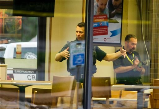 Crime lab technicians sweep a Wendy's in Omaha, Neb., for evidence, Wednesday, Aug. 27, 2014.