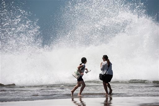 Cece, left, and Jennifer, of Orange County, run as big waves crash the shoreline, Tuesday, Aug. 26, 2014, at Venice Beach, Calif. (AP)