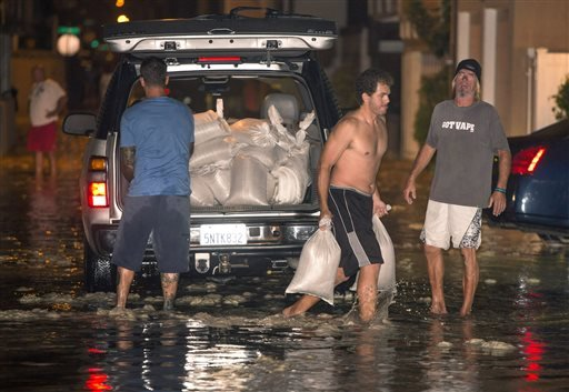In this Tuesday, Aug. 26, 2014 photo, residents carry sandbags to protect homes after high a tide and large waves caused heavy flooding in Seal Beach, Calif. (AP)