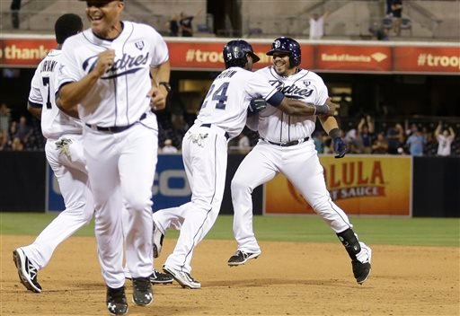 San Diego Padres' Rene Rivera, right, is swarmed by teammates after hitting an RBI single that gave the Padres a 3-2 win over the Milwaukee Brewers in 10 innings in a baseball game Wednesday, Aug. 27, 2014, in San Diego. (AP Photo/Gregory Bull)